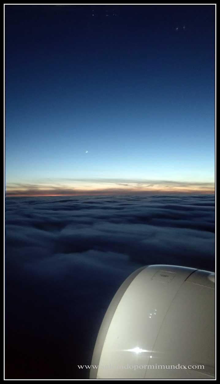 Vuelo sobre las nubes mientras anochece
